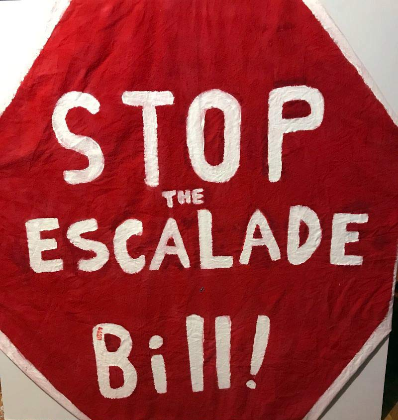 Red stop sign with words saying Stop the Escalade Bill!